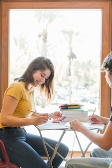 Teen couple doing homework near window