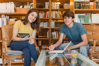 Teen couple in library looking at camera