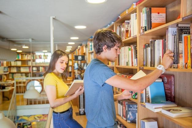 Teen couple reading books near bookshelves