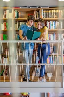 Teen couple reading on library balcony