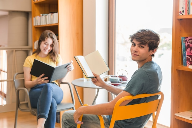 Teen couple reading in library