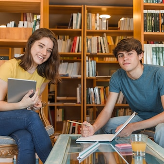 Teen couple with tablet doing homework