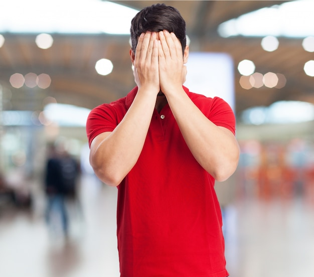Teen covering his face with hands