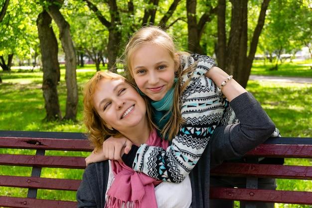 10대 딸이 공원 벤치에 앉아 어머니 뒤로 걸어가 갑자기 어깨를 껴안습니다.