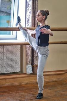 Подросток делает упражнения в танцевальном классе на скамейке