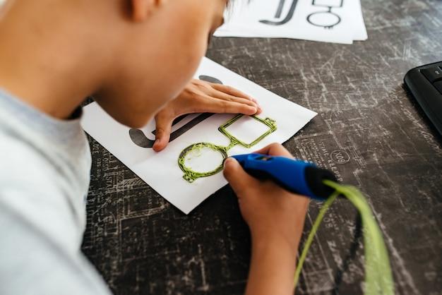 Teen draws 3d pen glasses