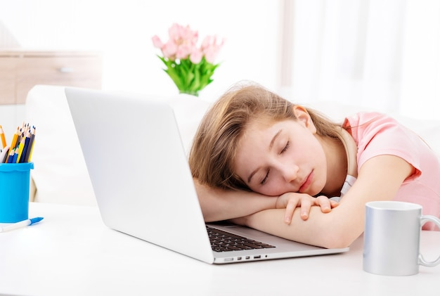 Teen fell asleep at the desk when working on laptop