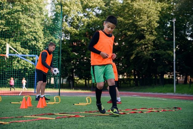 サッカーのトレーニング中に芝生ではしごドリルを実行している10代のサッカー選手