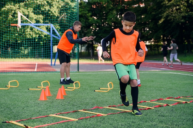 Teen football player running ladder drills on the turf during soccer training