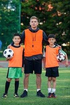 彼らのコーチとサッカー場に立っている10代のサッカー選手