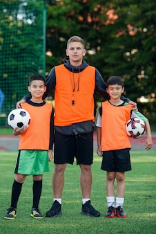 Teen football players standing on soccer field with their coach