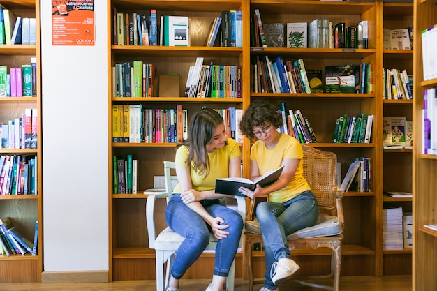 Teen friends reading book on chairs