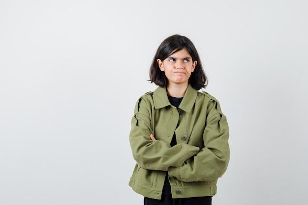 Ragazza teenager in giacca verde militare che tiene le braccia conserte, guardando lontano e guardando dispiaciuto, vista frontale.