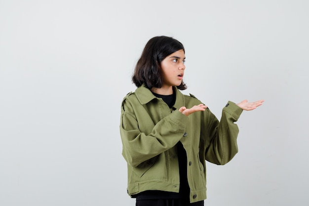 Teen girl in army green jacket pretending to show something, looking aside and looking wondered , front view.
