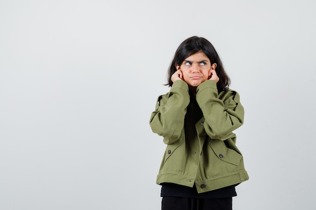 Teen girl in army green jacket pulling down her earlobes, looking away and looking concerned , front view.