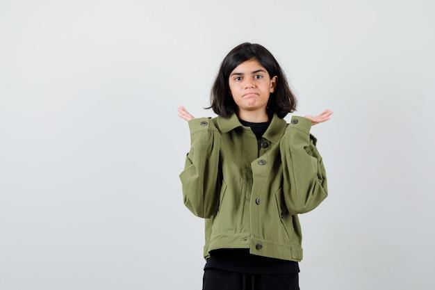 Ragazza teenager in giacca verde militare che mostra gesto impotente e sembra perplessa, vista frontale.