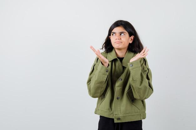 Ragazza teenager in giacca verde militare che mostra gesto impotente, alzando lo sguardo e guardando confusa, vista frontale.