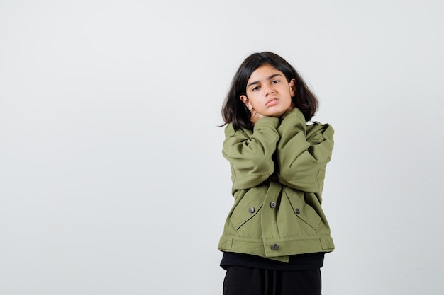 Teen girl in army green jacket suffering from neck pain and looking distressed , front view.
