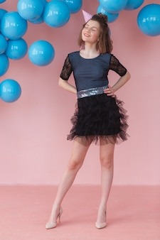 Teen girl in birthday cone posing on pink wall and blue balloons backdrop.