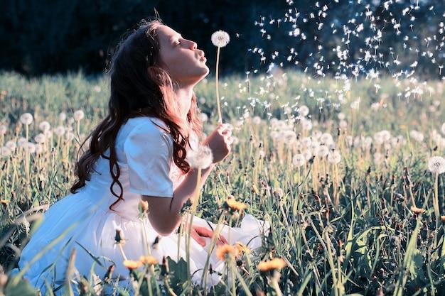 春の公園で花タンポポから種を吹く十代の少女