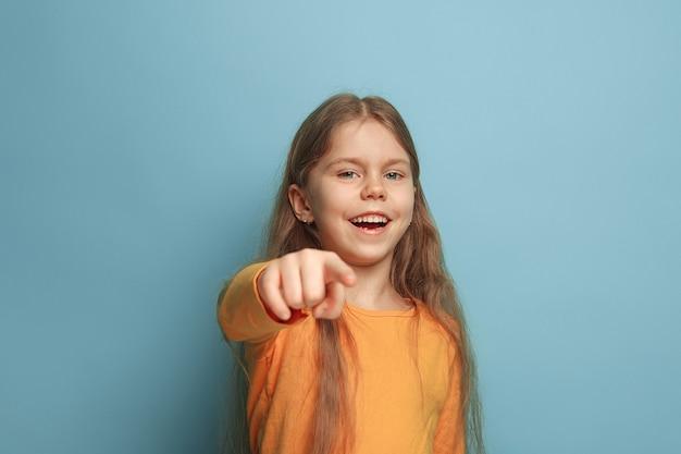 Ragazza teenager sull'azzurro. le espressioni facciali e le emozioni delle persone concetto
