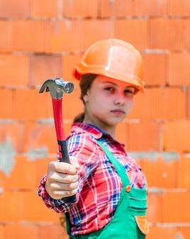 보호용 헬멧을 쓴 10대 소녀 빌더는 망치, 건축 도구를 사용합니다.