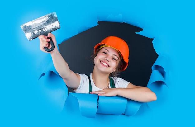 보호용 헬멧을 쓴 10대 소녀 빌더는 주걱, 건물을 사용합니다.
