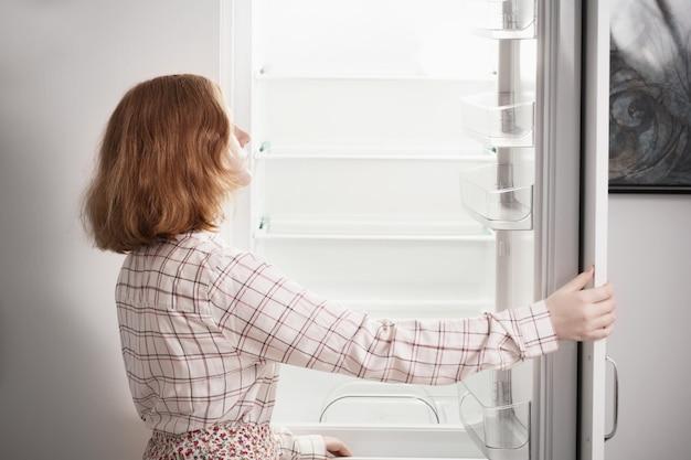 Девочка-подросток у пустого холодильника