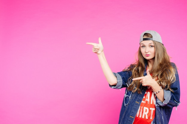 Teen girl in cap pointing at side and showing by fingers