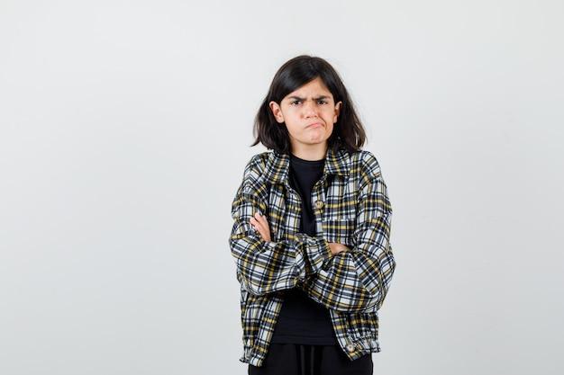 Ragazza teenager in camicia casual tenendo le braccia conserte, curvando il labbro inferiore e guardando scontroso, vista frontale.