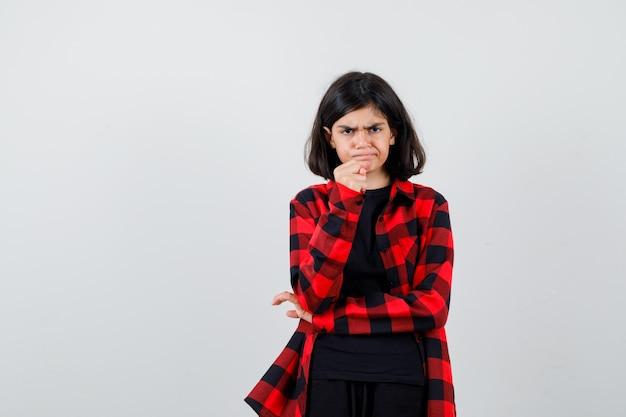 Ragazza teenager in camicia casual che avverte con il pugno e sembra aggressiva, vista frontale.