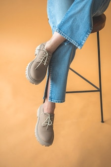 Teen girl in casual shoes. fashionable shoes on women feet in denim clothes. lifestyle and trendy design background photo
