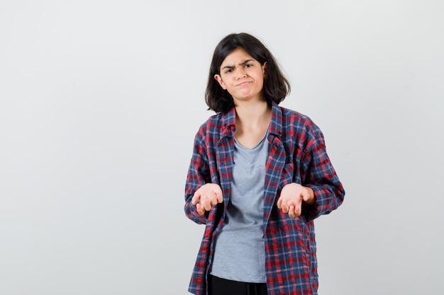 Ragazza teenager in camicia a scacchi che è dispiaciuta per la domanda stupida e sembra triste, vista frontale.