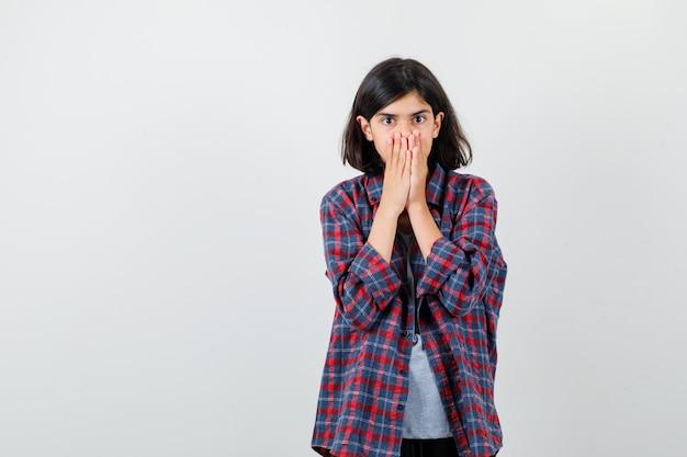 Ragazza teenager in camicia a scacchi che copre la bocca con le mani e sembra spaventata, vista frontale.