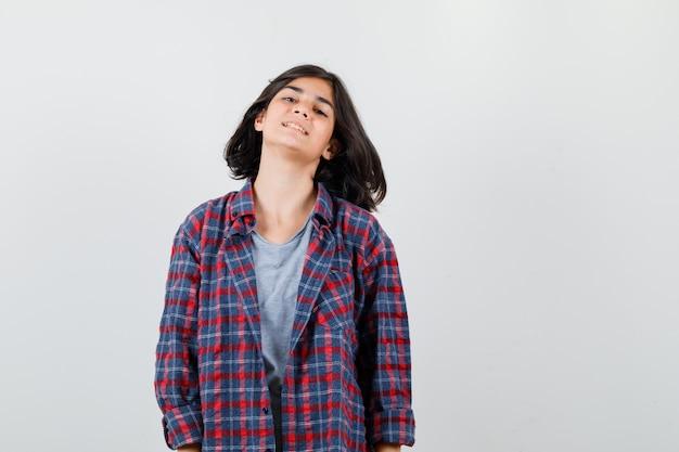 Ragazza teenager in camicia a scacchi e guardando soddisfatto, vista frontale.