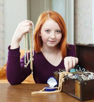 十代の少女が宝箱にビーズを選ぶ
