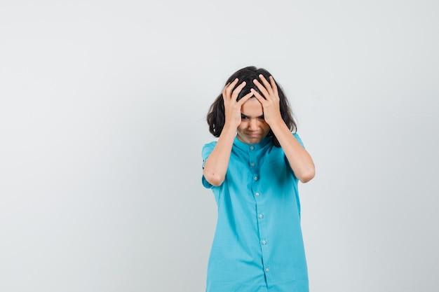 Девушка-подросток, обхватив голову головой в голубой рубашке и выглядя обеспокоенной.