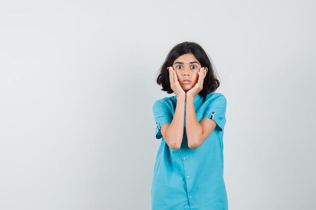 Девушка-подросток, обхватив лицо руками в синей рубашке и выглядя испуганной.