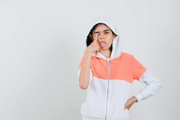 Ragazza teenager che chiude la sua palpebra con il dito mentre sporge la lingua in felpa e sembra pazza.
