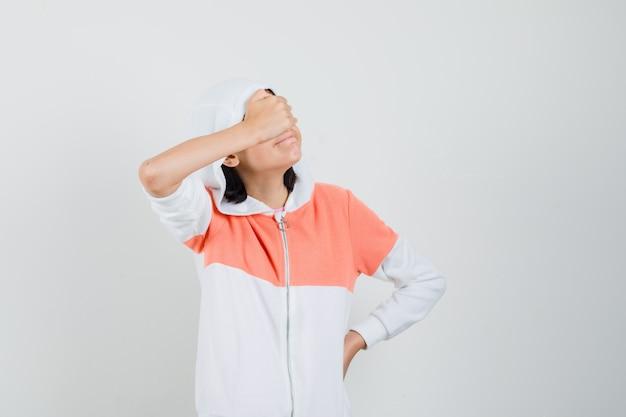 スウェットシャツと患者を探している手で目を覆っている十代の少女
