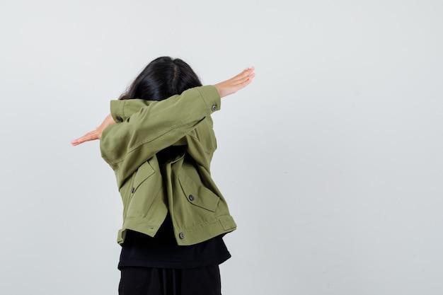 Tシャツ、緑のジャケットで腕で顔を覆い、悲しそうに見える10代の少女。正面図。