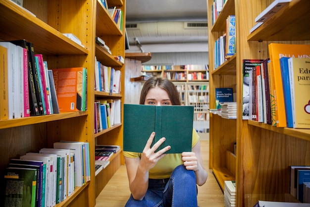 Teen girl covering face with book
