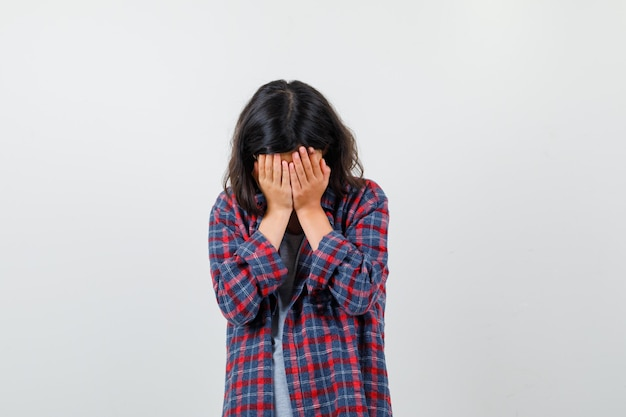 Teen girl covering face with hands in casual clothes and looking depressed , front view.