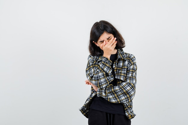 Teen girl covering mouth with hand in casual shirt and looking unwell , front view.