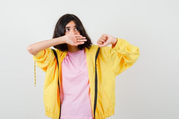 10대 소녀가 노란색 운동복, 티셔츠를 입고 손으로 입을 가리고 어리둥절한 표정을 짓고 있습니다.