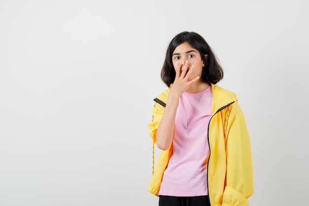 Девушка-подросток закрывает рот рукой в желтом спортивном костюме, футболке и выглядит потрясенной, вид спереди.