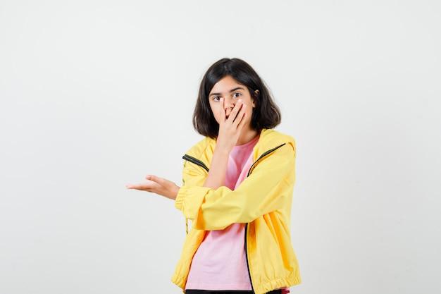 10대 소녀가 손으로 입을 가리고 노란색 운동복, 티셔츠를 입고 팔을 벌리고 놀란 표정을 짓고 있습니다.