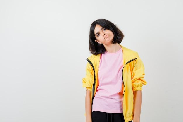 Ragazza teenager che curva il labbro inferiore in maglietta, giacca e sembra infastidita, vista frontale.