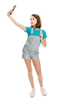 Teen girl in denim overalls and a blue t-shirt makes selfie on a smartphone. blogging and online communication. . full height. vertical.
