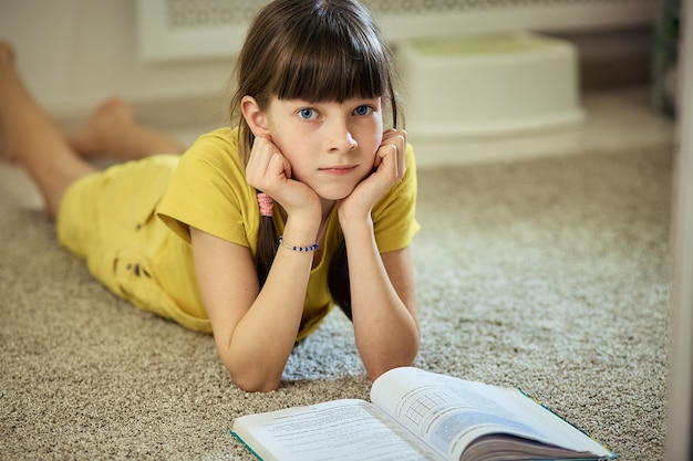 Девушка делает домашнее задание, сидя на ковре в своей комнате